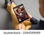 man reading magazine on tablet   Shutterstock . vector #1044398989