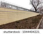 modern stone wall surrounding a ...   Shutterstock . vector #1044404221