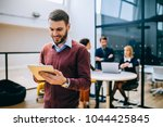 young businessman holding a... | Shutterstock . vector #1044425845