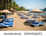 sun loungers on a beach in... | Shutterstock . vector #1044426631
