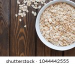 a white bowl of raw oat flakes... | Shutterstock . vector #1044442555
