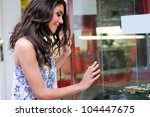 Portrait of an attractive young woman looking at the shop window - stock photo