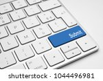 Small photo of Blue Submit push button on a white keyboard
