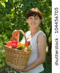 Happy young woman with vegetables harvest in garden - stock photo