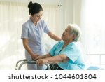 Stock photo asian young nurse supporting elderly patient disabled woman in using walker in hospital elderly 1044601804