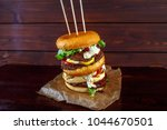 Small photo of Big beef burger on wooden background with tomato souse, white souse, fresh greens, buns
