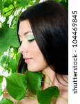 Beautiful woman with spring green leaves. Skincare - stock photo