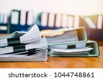 Small photo of Stack of business report paper file on modern white office desk with bokeh background.