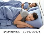 young couple sleeping in bed at ...   Shutterstock . vector #1044780475