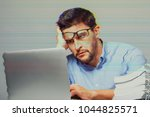 pensive sad man sitting at the... | Shutterstock . vector #1044825571