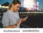 Small photo of Hipster girl with smartphone send comment in social network spending leisure in amusement park with shining ferris wheel, young woman sending message via cellphone recreating in Santa Monica pier