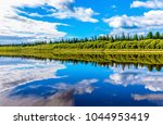 forest river sky clouds... | Shutterstock . vector #1044953419