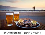 beer and mussel at the sunset | Shutterstock . vector #1044974344