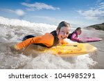 two little girls are smiling... | Shutterstock . vector #1044985291