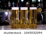 three mugs with a cold beer on... | Shutterstock . vector #1045032094