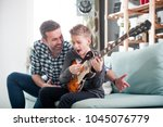 son and father playing electric ...   Shutterstock . vector #1045076779