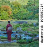 """Small photo of KYOTO, JAPAN - OCTOBER 31, 2015: A Japanese lady in traditional kimono clothing admiring a beautiful garden which locals call the """"Place of Scenic Beauty"""" at Murin-an Villa."""