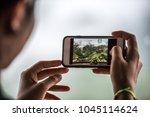 tourist hand holding mobile... | Shutterstock . vector #1045114624