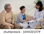 smiling senior couple sitting... | Shutterstock . vector #1045201579