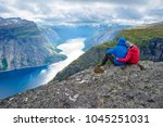 couple sits on rock and looks... | Shutterstock . vector #1045251031