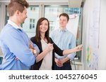 Small photo of Businesswoman Sticking Adhesive Notes While Standing With Collea