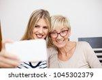 senior mother and her daughter... | Shutterstock . vector #1045302379