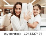 Small photo of Smiling little girl with beautiful mother hugs pillows in store of orthopedic mattresses. Testing softness of pillow. Check softness of orthopedic pillow.