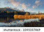 Small photo of fantastic foggy landscape at Germanian Alps. Colrful Clouds on the Blue Sky over Zugspitze mountains at early morning in autumn, Bavaria, Germany. Fresh grass on foreground. Awesome nature background