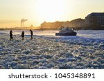 Small photo of Rescue hovercraft MOE at sunset warns pedestrians about the danger of crossing the Neva river on the ice in March in Saint-Petersburg.