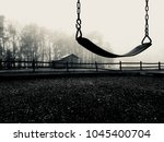 Small photo of A black and white of a single empty swing on cold lonesome foggy morning with a barn and broken wooden fence in the background. Could signify loss or grief.