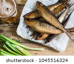 Stock photo a few smoked baltic herring on white paper and beer in glass on an old wood background top view 1045516324