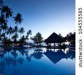 Amazing sunrise at swimming pool wit palms background - stock photo