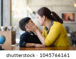 asian mother going to kiss her... | Shutterstock . vector #1045766161