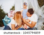 happy mom and dad hold little... | Shutterstock . vector #1045794859