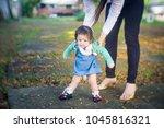 baby girl walking in the park... | Shutterstock . vector #1045816321