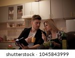young couple reading recipe... | Shutterstock . vector #1045843999