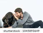 man playing with a dog on a... | Shutterstock . vector #1045893649