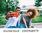 Small photo of Beautiful african american girl with curly hair posing for pictures with her boyfriend using modern smartphone, couple in lovemaking selfie together enjoying resting on spring sunny day in park