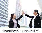 two of businesswoman hi five... | Shutterstock . vector #1046023129