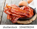 hot fried bacon pieces in a... | Shutterstock . vector #1046058244