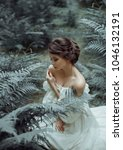 Small photo of The princess sits on the ground in the forest, among the fern and moss. On the lady is a white vintage dress with a deep cutout, beautifully emphasizes a chest. Art photo. Emotions of melancholy