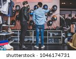 two men in motorcycle shop.... | Shutterstock . vector #1046174731