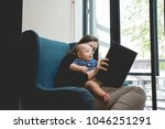 mother reading a book to her...   Shutterstock . vector #1046251291