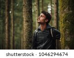 young handsome man walking in a ... | Shutterstock . vector #1046294674