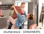 happy mature couple dancing in... | Shutterstock . vector #1046448391