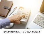 Small photo of businessman dial digital telephone with office background