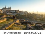 man looking at the sunrise over ... | Shutterstock . vector #1046502721