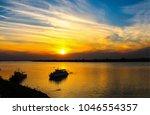 sunset river boat silhouette... | Shutterstock . vector #1046554357