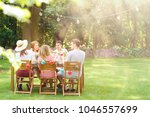 group of smiling friends eating ... | Shutterstock . vector #1046557699
