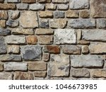 Small photo of Old stone wall, built of coarse, uncouth boulders of square shape of various sizes.